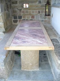 überdachter Sitzplatz mit Marmortisch unter einem Balkon