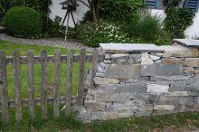 Holzzaun mit angrendender Granitmauer