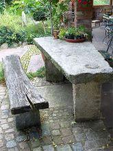 Sitzplatz mit Holzbank und antiker Granittischplatte