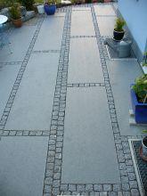 Terrasse mit Granitplatten und Basalteinfassung